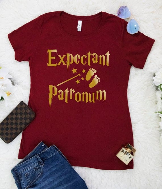 Cute Pregnancy Announcement Shirts for Harry Potter Fans. Maroon shirt reads Expectant Patronum in gold.